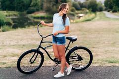 Portrait of attractive young woman in blue shirt with cool beach cruiser bike Stock Photos