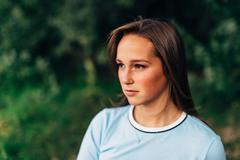 portrait of an attractive young woman looking away from camera staring seriou - stock photo
