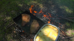 Argentina Picnic - Chef turns steaks over campfire Stock Footage