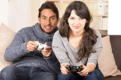 young cute couple playing video games - stock photo