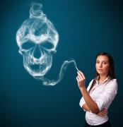 Young woman smoking dangerous cigarette with toxic skull smoke - stock photo