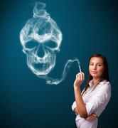 Young woman smoking dangerous cigarette with toxic skull smoke - stock photo