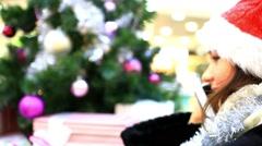Yong woman in cap Santas talking on the phone near Christmas tree. HD. 1920x1080 Stock Footage