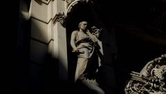 Greek Statue on building facade covered by shadows Stock Footage