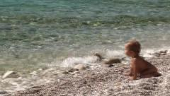Child waits at the seashore while adult is swimming Stock Footage