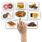 Woman hand uses touch screen interface with food. Stock Photos