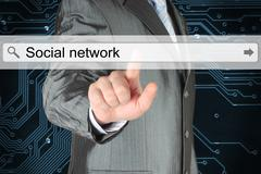 Businessman pushing virtual search bar with social network words . Stock Photos