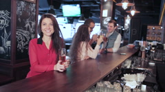 Girl with a glass of beer at the bar welcomes friends - stock footage