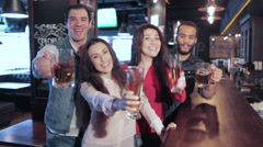Four old friends at the bar with a glass of beer is welcomed new friends - stock footage