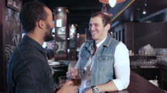 Two gay friends at the bar with a beer and then smiling at the camera - stock footage