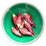 dryed chili peppers in a green bowl white background - stock photo