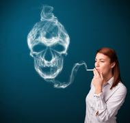 Young woman smoking dangerous cigarette with toxic skull smoke Stock Photos