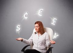young lady sitting and juggling with currency icons - stock photo