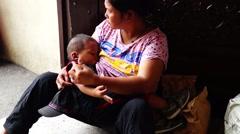 Breast Feeding sitting on sidewalk - stock footage