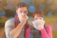 Stock Photo of Composite image of couple blowing noses into tissues