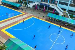 sportsmen train on blue stadium - stock photo