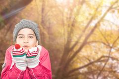 Composite image of wrapped up little girl blowing over hands - stock photo