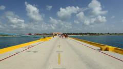 People walking towards an island on a pedestrian street in the middle of ocean Stock Footage
