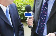 Man being interviewed by journalist for tv or radio Stock Photos