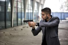 Detective or mobster or policeman aiming a firearm Stock Photos