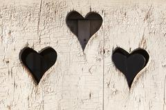 Heart shape look out on wooden door to outhouse. Stock Photos
