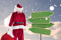 Composite image of santa carrying sack of gifts Stock Photos