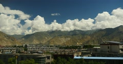 4k lhasa building in foot of Tibet mountain,cloud mass rolling over mountaintop Stock Footage