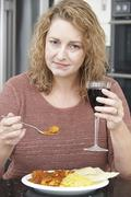 guilty woman eating takeaway curry and drinking wine - stock photo
