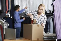 Couple running online clothing store packing goods for dispatch Stock Photos