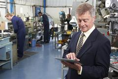 Owner of engineering factory using digital tablet with staff in background Stock Photos