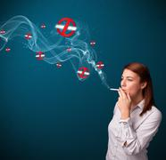 Young woman smoking dangerous cigarette with no smoking signs - stock photo