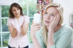 Mother arguing with teenage daughter over use of mobile phone Stock Photos