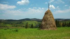 Time lapse of clouds and haystack on green field Stock Footage