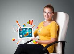 Woman holding modern tablet with colorful diagrams and graphs Kuvituskuvat