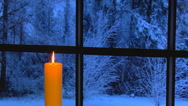 Stock Video Footage of Golden candle in front of window snowing outside