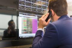 Stock trader looking at computer screens. - stock photo