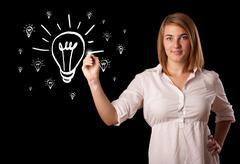 Woman drawing light bulb on whiteboard Stock Photos