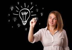 Woman drawing light bulb on whiteboard - stock photo