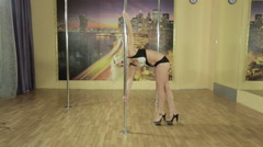 Girl in excellent physical shape performs trick on pole Stock Footage