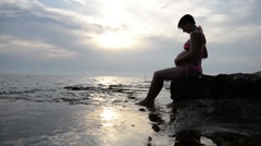 pregnant woman in a swimsuit sitting in profile cradling her swollen belly - stock footage