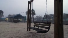 Empty swing moving by itself on foggy beach Stock Footage