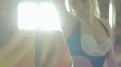 Beautiful blond sexy moves near pole in dimly lit room Stock Footage