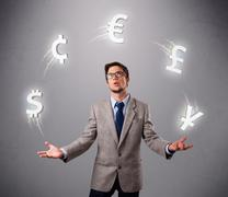 young man standing and juggling with currency icons - stock photo
