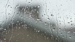 Close up image of rain drops falling on a window Stock Footage