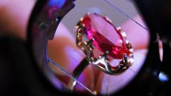 Gold ring with red ruby through the measuring glass. Close up Stock Footage