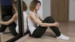 Sad young woman sitting on the floor Stock Footage