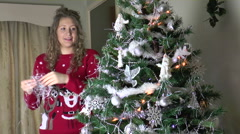 Pretty young woman putting tinsel on her Christmas tree Stock Footage