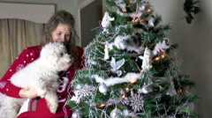 Pretty young woman and dog at her Christmas tree Stock Footage