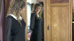 Pretty young woman looking in mirror - dislikes dress Stock Footage