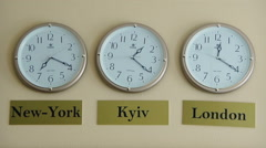 Three clocks showing the time zones of New York, London and Kyiv Stock Footage